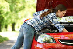 Driver femminile ripartito Looking Under Hood Of Car Immagine Stock