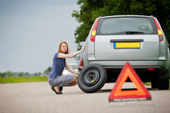 Driver fixing flat tire. A female driver about to fix a flat tire on her station wagon car Stock Photos