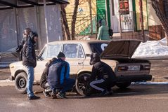 The driver with friends change the punctured wheel by car. Tyumen, Russia - March 1, 2019: The driver with friends change the punctured wheel by car. Holodilnaya royalty free stock images