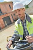 Driver in front construction machinery on building site. Driver in front of construction machinery on building site Royalty Free Stock Image