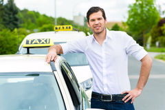 Driver in front of taxi waiting for clients Royalty Free Stock Images