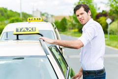 Driver in front of taxi waiting for clients stock photos