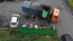 Driver of garbage truck loading container with garbage into its bins stock video