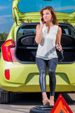 Driver girl calling mechanic standing near the  car Royalty Free Stock Photography