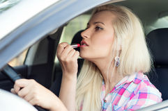 Driver a girl paints her lips at the wheel the car Stock Image