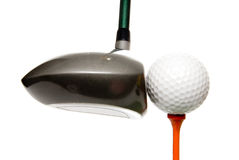 Driver and golf ball. Closeup of the head of a driver just before it hits a golf ball on a wood tee, isolated on a white background Stock Photography