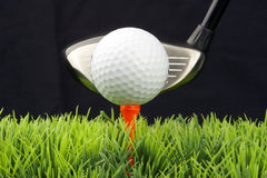 Driver and golfball. White golfball on tee, driver behind, isolated on black background Royalty Free Stock Photo