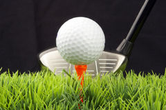 Driver and golfball. White golfball on tee, driver behind, isolated on black background Stock Images