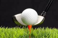 Driver and golfball. White golfball on tee, driver behind, isolated on black background Royalty Free Stock Image