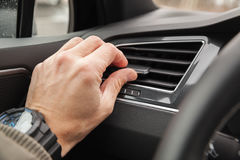 Driver hand on air ventilation grille. With power regulator, modern car interior detail Stock Images