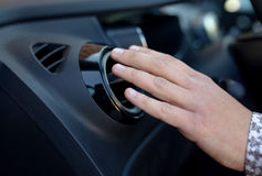 Driver hand on air ventilation grille with power regulator, modern car interior detail. Driver hand on air ventilation grille with power regulator, checking the Royalty Free Stock Photos