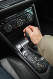 Driver hand holds gear lever, automatic. Driver hand holds gear lever of modern luxury car. Close up photo with selective focus royalty free stock images