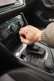 Driver hand holds gear lever of crossover. Driver hand holds gear lever of modern luxury crossover car. Close up photo with selective focus stock images
