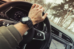 Driver hand holds steering wheel of crossover car. Driver hand holds steering wheel of luxury crossover car. Close-up photo with selective focus and warm tonal Stock Photos