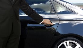 Driver hand opening car door. Chauffeur hand opening black car door while waiting for passenger Royalty Free Stock Photography