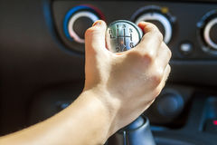 Driver hand shifting gear shift knob manually, selective focus.  Royalty Free Stock Image