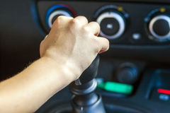 Driver hand shifting gear shift knob manually, selective focus.  Stock Images