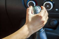 Driver hand shifting gear shift knob manually, selective focus.  Royalty Free Stock Photography