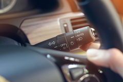 Driver hand using switch arm stick control light sign. Turn left or left and open mode of headlight car Stock Photos