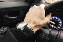 Driver hand with wrist watch on a steering wheel Stock Photography