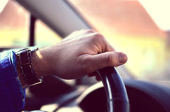 Driver hands holding steering wheel. Male driver hands holding steering Wheel and driving Royalty Free Stock Images