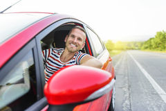 Driver. Happy smiling man in new red car on the road Royalty Free Stock Images