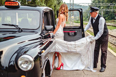 Driver helping bride to enter the car. By holding her dress Royalty Free Stock Images