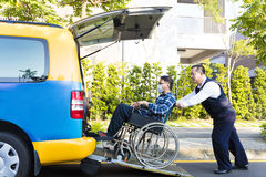 Driver helping man on wheelchair getting into taxi Stock Photo