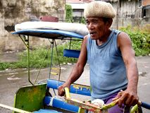 A driver in his pedal powered tricycle, also known locally as. TACLOBAN CITY, PHILIPPINES - NOVEMBER 9, 2015: A driver in his pedal powered tricycle, also known Stock Photography