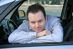 Driver looking at you. Young and handsome driver looks at you gently from his left car window Stock Photography