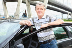 Driver maggiore con il tasto di accensione vicino all'automobile Immagini Stock