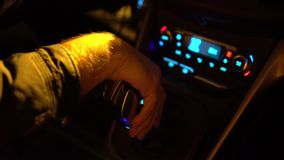 Driver man controls auto and hold hand on gear shifter or gear knob gear stick at night shadows road lights. Close up of. Driver man controls auto and hold hand stock footage