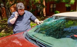 Driver, man making phone call after car accident. With broken windshield man crash insurance reporting glass mobile damage collision claim male traffic dented stock photo