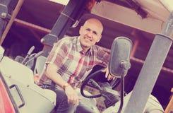 Driver maschio che fa funzionare trattore moderno Fotografia Stock
