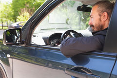 Driver of modern suv looks in open car window Stock Photo