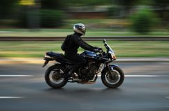 The driver of the motorcycle. Driving fast, fast motorcycle, riding down the street stock image