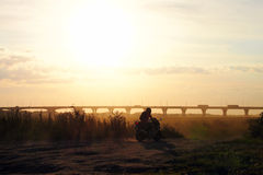 The driver of the motorcycle. The motorcyclist moves along the river at sunset Stock Images