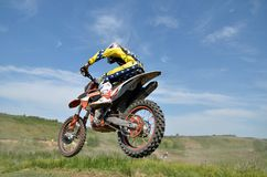 Driver motorcycle MX flies over hill Stock Photos