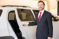 Driver opening the door for you. Portrait of a handsome and professional driver opening the car door for one of his clients stock image