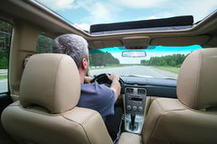 Driver operates car on the country highway Stock Images
