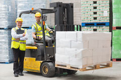 Driver operating forklift machine next to his manager Royalty Free Stock Image