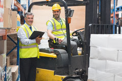Driver operating forklift machine next to his manager Stock Photo
