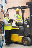 Driver operating forklift machine next to his manager. In warehouse Royalty Free Stock Images