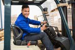 Driver operating forklift machine in warehouse Stock Photos
