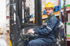 Driver operating forklift machine in warehouse Stock Image