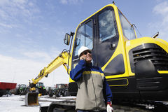 Bulldozer and driver. Driver, operator standing in front of new bulldozer, digger Royalty Free Stock Image