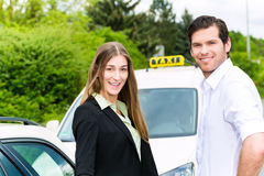 Driver in passenger in front of taxi Royalty Free Stock Image