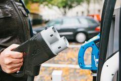 The driver picks up a cable to charge the electric vehicle. A modern and eco-friendly mode of transport that has spread Royalty Free Stock Images