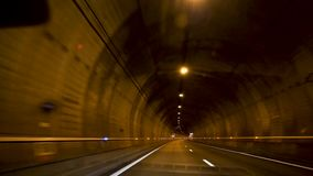 Driver point of view of endless tunnel. Driver point of view driving fast in the illuminated endless tunnel with reinforced security signs and ventilation tubes stock footage
