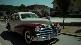 Driver of polished vintage car is talking to a blue-collar worker stock video footage
